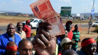 Someone holding a rand not in South Africa - archive shot