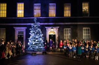 British Prime Minister Theresa May and Isabel Milns, Jade Winsor and Sophie Brazil from schools in Maidenhead switch on the Christmas tree lights outside Number 10, Downing Street