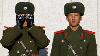 North Korean soldiers look at South Korea across the Korean Demilitarized Zone (DMZ), on December 22, 2011 in Panmunjom, South Korea.