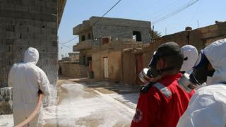 Members of the civil defence spray and clean areas in the town of Taza, around 220 kilometres north of the capital Baghdad, on 13 March 2016, that might have been contaminated in a chemical attack carried out by the Islamic State (IS) group the previous week.