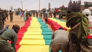 Soldiers stand near caskets at a funeral ceremony for victims of January 18 suicide bomb attack that ripped through a camp grouping former rebels and pro-government militia in Gao, in the troubled northern Mali, on January 20, 2017 in Gao