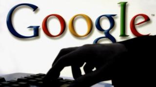 Woman at keyboard with Google logo behind