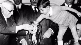 El presidente de la FIFA, Jules Rimet, es asistido por un niño durante el sorteo de la Copa del Mundo de 1938.