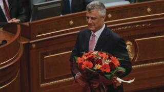 Hashim Thaci holds holds flowers after being elected Kosovo's president