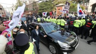 Police contain supporters of Park Geun-hye as she leaves in a car her home in Seoul. Photo: 21 March 2017