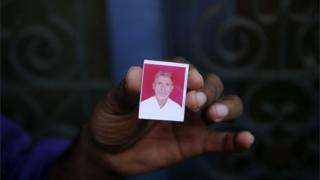A relative holds a photograph of slain Indian villager Mohammad Akhlaq at his home in the village of Bisada,