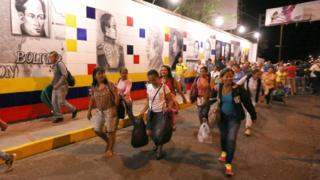 People living in Venezuela begin crossing into Colombia from the city of Cucuta in the early hours of Saturday