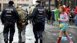 Policemen arrest a man during Weiberfastnacht celebrations as part of the carnival season on February 4, 2016 in Cologne, Germany.