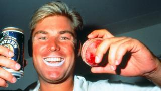 Classic Warnie: Shane sports his signature lip zinc and celebrates with a beer after a match in the 1990s