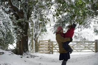 A woman holds her child whilst in the snow at Box Hill
