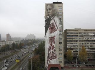 Guido van Helten's mural on the side of an 18-storey apartment block in Kiev, Ukraine