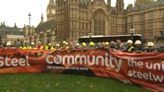 Dozens of steelworkers met outside Parliament to unfurl a Save Our Steel banner