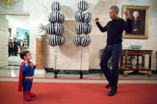 Left, a small child dressed in a superman outfit attempts to flex his muscles, while right, Mr Obama shows him how the pose is done.
