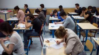 French students work on the test of philosophy as they take the baccalaureat exam (high school graduation exam) on June 17, 2013 at the Arago high school in Paris