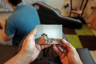 Person holding a picture of a man and a child with guitar