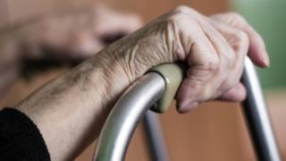 Elderly hands on a walking frame