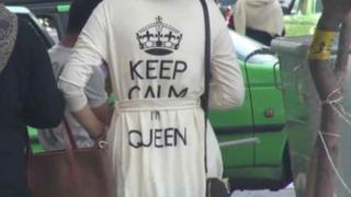 """A video report by Iran's Fars news agency shows a woman with a top bearing the slogan """"Keep calm, I'm queen""""."""