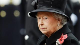 The Queen dressed in black jacket and black hat