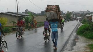 Man carries mattresses out of violence affected area