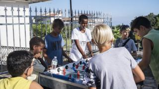 Children play table football in Riace