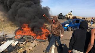 Demonstrators stand next to burning tires as armed soldiers and law enforcement officers assemble on Thursday, Oct. 27, 2016