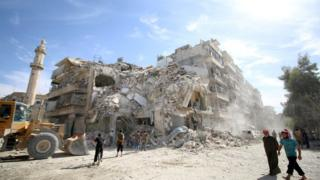 People inspect a damaged site after an air strike Sunday, October 17, in the rebel-held besieged al-Qaterji neighbourhood of Aleppo
