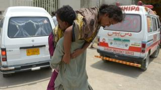 A Pakistani man carries a heatstroke victim into a hospital in Karachi on June 23, 2015
