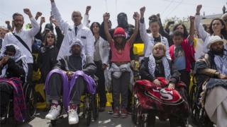 A crowd of people holding their fists high, with the hunger strikers ahead of them in wheelchairs