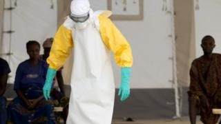 A health worker wearing a protective suit treats Ebola patients in West Africa
