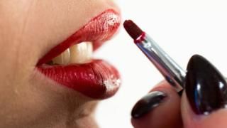 Woman applying bright red lipstick