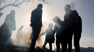 Refugees stand near a makeshift fire as they wait to be allowed to cross the border to Macedonia in the northern Greek border station of Idomeni, on Wednesday, 2 March 2016