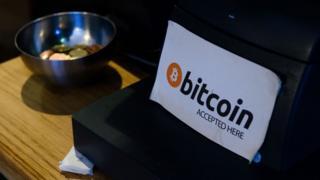 """Bir kafede kasanın yanında """"Bitcoin kabul edilir"""" yazısı."""