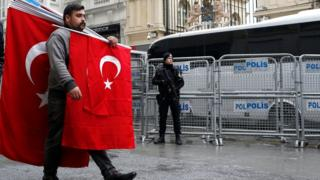 A man carrying Turkish flags walks past a Turkish armed riot policeman in front of the Dutch Consulate in Istanbul, Turkey, 13 March 2017.