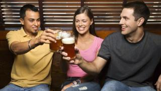 Two men and a woman drinking beer