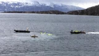 A boat picks up tourists from the water after an accident in Harstad harbour in Northern Norway.