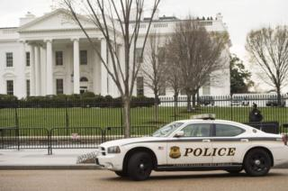 Members of the Secret Service Uniformed Division patrol alongside the security fence around the perimeter of the White House in Washington, DC, on March 18, 2017.