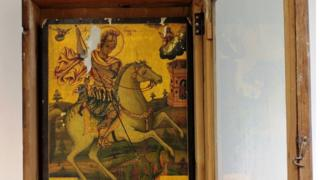 a Byzantine image of Saint George, in recognisable golden painting style, sits in a wooden frame