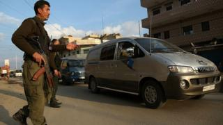 Members of the Kurdish security forces ,known as the Asayish, check vehicles on 16 December 2015 in the north-eastern Syrian city of Qamishli
