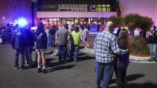 """People stand near the entrance on the north side of Crossroads Center mall between Macy""""s and Target as officials investigate a reported multiple stabbing incident, Saturday, Sept. 17, 2016, in St. Cloud, Min"""