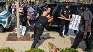 This photo provided by OC Weekly shows counter-protesters scuffling with a KKK member as he stabs an attacking protester, center, as members of the KKK try to start an anti-immigration rally at Pearson Park in Anaheim on Saturday, Feb. 27, 2016