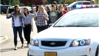 Students, staff and faculty are evacuated from Umpqua Community College in Roseburg, Ore. Thursday, Oct. 1, 2015, after a deadly shooting.