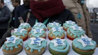 A demonstrator holds a tray of decorated cakes at a protest by junior doctors outside the Frimley Park Hospital in Frimley, south-west London.