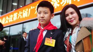 Male student with his mother attending a government meeting in China.