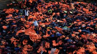 Volunteers stand on a pile of lifejackets left behind by refugees and migrants who arrived to the Greek island of Lesbos
