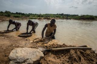 Three men sift through mud with circular sieves