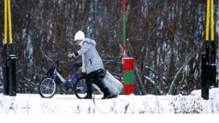 A migrant with a bicycle and a suitcase crosses the border between Norway and Russia in Storskog near Kirkenes in Northern Norway, 16 November 2015.