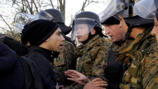 A migrant talks with a Macedonian policeman as he and other migrants wait to cross Greece's border with Macedonia