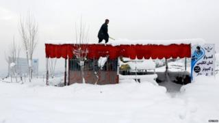An Afghan man removes snow from his shop on the outskirts of Kabul