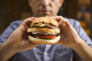 Homem comendo hambúrguer
