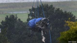 The damaged remains of the fuselage of a Hawker Hunter fighter jet are lifted by crane